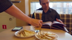 Stock Video Footage of Young man Choosing from a Restaurant Menu  and drinking beer while waiter bring