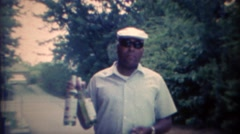 1969: African man clowning rum alcohol liquor bottles. Stock Footage