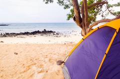 Small campsite with a two person tent setup in sand on beautiful beach, pacific - stock photo