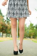 Classy woman visible from waist down wearing fashionable skirt and elegant black Stock Photos