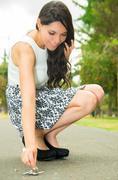 Classy woman wearing fashionable skirt and elegant black high heels bending down - stock photo