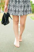 Classy woman wearing fashionable skirt walking barefeet on asfalt surface - stock photo
