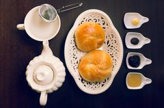 Cup of tea, hot water decanter and nice white bowl with two beautiful breads Stock Photos
