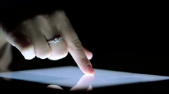 Close-Up of Female Finger on the Ipad Screen in the Dark Stock Footage