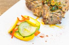 Beautifully cooked cutlet with chimichurri topping placed upon white plate - stock photo