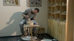 Potter Molds a Pot Spatula Rotating a Wheel Man is Working at Pottery Wheel is - stock footage