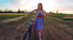 Cheerful young girl walks a vintage bicycle between fields of tulip flowers Stock Footage