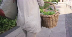 Beautiful woman shopping basket healthy fresh vegetables walking in city - stock footage