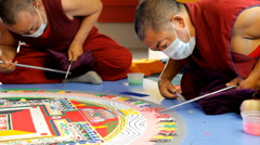 Tibetian monk constructing mandala from colored sand on Week of Tibetian Culture Stock Footage