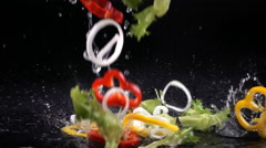 Fresh vegetables falling with water in slow motion Stock Footage