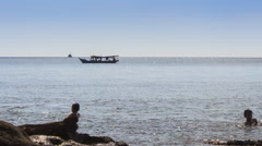 People Swim in Sea by Rock Beach Boat Drifts past - stock footage