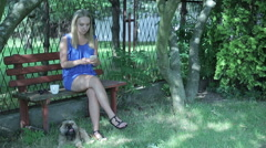 Young woman stting on the bench and texting  Stock Footage