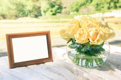 yellow roses in glass jar with wedding picture frame - stock photo