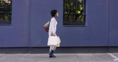 Beautiful Mixed race woman carrying shopping bags walking through city Stock Footage