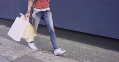 Beautiful woman carrying shopping bags walking through city - stock footage