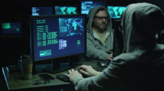 Two hackers in hoods work on a computers with maps and data on display screens Stock Footage