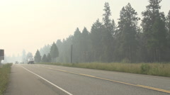 transportation, logging truck on smoky sky filled narrow highway - stock footage