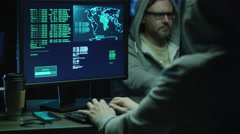Two hackers in hoods work on a computers with maps and data on display screens - stock footage