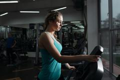 Pretty woman walking on treadmill in fitness center Stock Photos