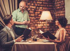Stock Photo of Waiter taking order from stylish wealthy couple in restaurant.