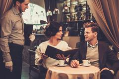 Stylish wealthy couple with menu in a restaurant. - stock photo
