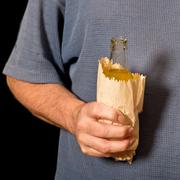 Drinker holds a bottle in the paper bag Stock Photos