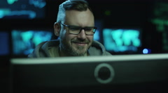 Portrait footage of concentrated male employee working on computer in dark room - stock footage