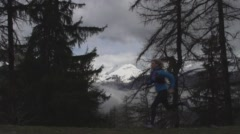 Women Running in Alpine Forest with Snowy Mountains. Stock Footage