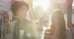 Two beautiful friends walking using smart phone technology in sunny city Stock Footage