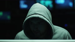 Male hacker working on a computer while wearing a hood so his face is hidden - stock footage