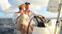 Couple on a sailboat sitting at wheel Stock Footage