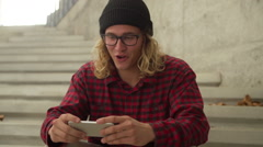 Young Happy Hipster Man Laughing While Watching Funny Video On Iphone - stock footage