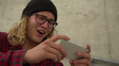 Young Happy Hipster Man Laughing While Watching Funny Video On Iphone Outside - stock footage