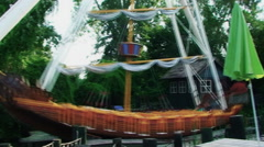 An amusement Park, a large swing in the form of a ship gently sways Stock Footage