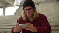 Young Hip Man Laughing While Looking At Phone Outside - stock footage