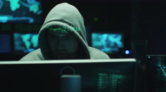 Male hacker working on computer while green code characters reflect on his face Stock Footage