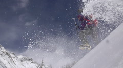 Mountaineer Leaps from Snowy Mountainside Stock Footage