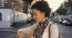 Beautiful Mixed race woman using smart watch technology walking through city - stock footage