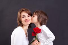 Young kid giving gorgeous red rose to his mom Stock Photos