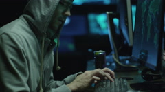Male hacker in a hood works on a computer with maps and data on display screens - stock footage