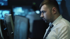 Two IT programmers are working on computers in a dark office room Stock Footage