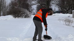 Man with snow shovel on the snovy road in winter Stock Footage