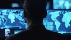 Male employee monitors maps and data on computer display screens in dark office - stock footage