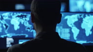 Stock Video Footage of Male employee monitors maps and data on computer display screens in dark office