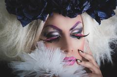 Drag queen with spectacular makeup, glamorous trashy look, posing happily and Stock Photos