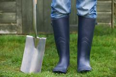 Close Up Of Man Wearing Wellingtons Holding Garden Spade - stock photo
