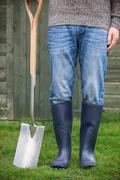 Close Up Of Man Wearing Wellingtons Holding Garden Spade Stock Photos
