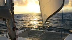 Sailboat with sails open cruising at sunset Stock Footage