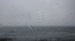 Rain drops falling on car window against ocean waves on a rainy day Stock Footage