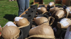 Close-up of packaged fireworks being placed on ground mortars before a show Stock Footage